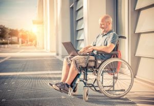 Disabled man on the wheelchair working with laptop computer outdoors - Handicapped senior man outside the hospital relaxing at sunset